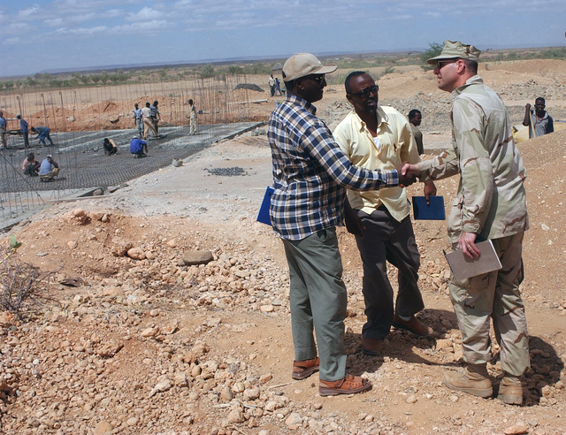 Mr. Alemayehu Mekonin (left), a Water Engineer at the Gode Waste Water Treatment Facility, greets US Navy (USN) Commander (CDR) Paul Vandenberg, an Engineer assigned to Naval Mobile Construction Battalion 7 (NMCB-7), as he arrives at the Facility in Gode, Ethiopia (ETH). Mr. Mekonin is overseeing a construction project to add capacity to the area's water treatment ability. CDR Vandenberg is doing preliminary research as part of Combined Joint Task Force (CJTF) Horn of Africa, which is interested in aiding the people of Ethiopia as they improve their quality of life. In the center is Abdi Reshid Mohamed Omer, the head of Ethiopia's Mines and Energy Department