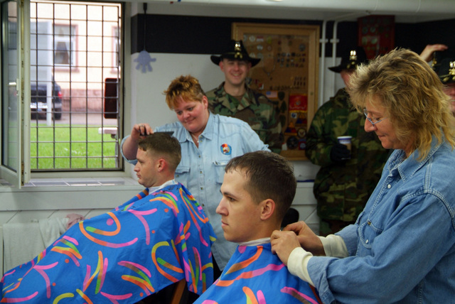 CAPT. Felix, and SPC. Bosold choose to have haircuts after LT. COL. John A. Peeler and Command SGT. MAJ. David S. Davenport Sr. hold a haircut inspection. They are from 1ST Armored Division, 1ST U.S. Cavalry Regiment and are participating in a Spur Ride held April 3 and 4, 2006 in Buedingen Germany. (U.S. Army photo by Martin Greeson) (Released)