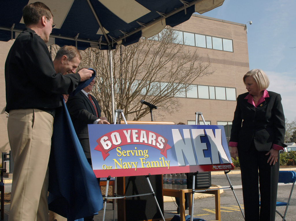 Members of the Official Party reveal a banner during a Celebration for the Navy Exchange's (NEX) 60th anniversary, held at Virginia Beach, Virginia (VA). The Navy Exchange (NEX) has been serving Sailors and their families for 60-years. Pictured left-to-right: US Navy (USN) Rear Admiral (RADM) (Upper Half) Robert E. Cowley III, Commander, Navy Exchange Service Command (NEXSC); USN RADM (Upper Half) Rick Ruehe, Commander, Navy Region Mid-Atlantic; and US Congresswoman The Honorable Thelma Drake (R-VA.)