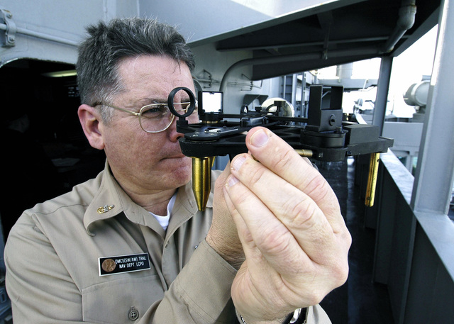 Onboard the US Navy (USN) Nimitz Class Aircraft Carrier, USS ABRAHAM LINCOLN (CVN 72), SENIOR CHIEF Quartermaster (QMSC) John Trail, demonstrates the use of a Stadimeter, a navigational instrument used to determine the distance from one object to another. The REAGAN and embarked carrier Air Wing 14 (CVW-14) is currently on its maiden deployment conducting Maritime Security Operations (MSO) in the Persian Gulf region as part of a scheduled six-month deployment