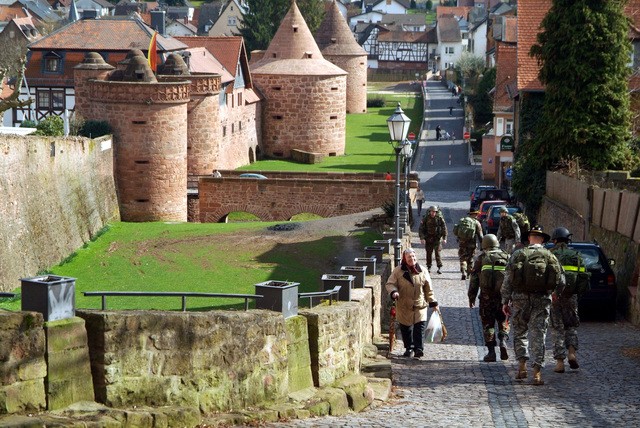 Team 4 walks past the Buedingen Schloss on their way to the next challenge. They are from 1ST Armored Division, 1ST U.S. Cavalry Regiment and are participating in a Spur Ride held April 3 and 4, 2006 in Buedingen Germany. (U.S. Army photo by Martin Greeson) (Released)