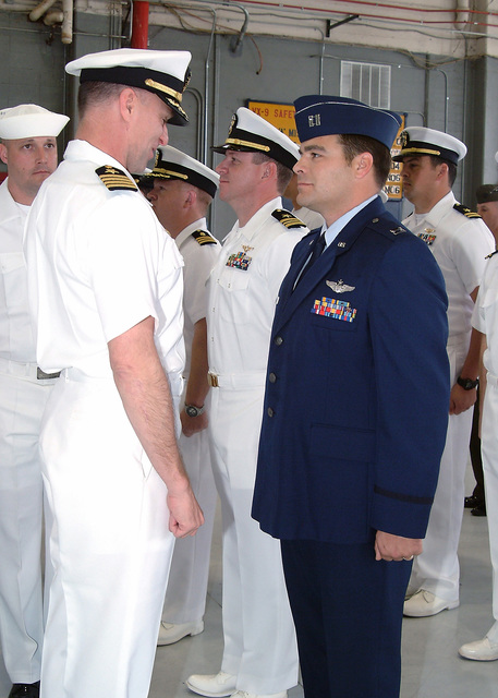 US Navy (USN) Captain (CAPT) Bruce Fecht (foreground left), Commanding Officer (CO), Air Test and Evaluation Squadron 9 (VX-9) inspects the uniform of US Air Force (USAF) Captain (CPT) Jeffery Alexander, during a morning inspection at Naval Air Weapons Station (NAWS) China Lake, California (CA)