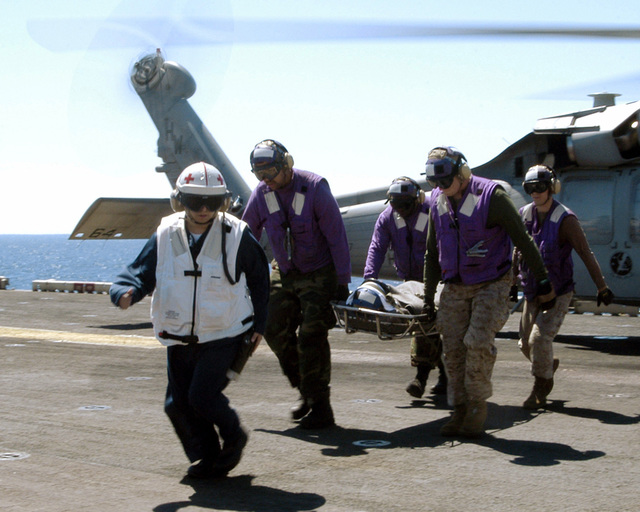 US Navy (USN) Hospital Corpsman (HM) Jose G. Rodriguez, stationed on the USN Wasp Class Amphibious Ship USS IWO JIMA (LHD 7), leads a stretcher bearer medical evacuation flight team from a SH-60 Seahawk helicopter. On the stretcher was a USN Sailor from the USN Oliver Hazard Perry Class Frigate USS KLAKRING (FFG 42)