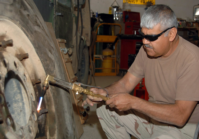 SGT. Felipe Capristo from the 445th Civil Affairs Battalion, Calif. USAR, uses a heat torch to repair a wheel on a 5 ton at the motor pool.  (U.S. Army photo by PFC. William Servinski II) (Released)