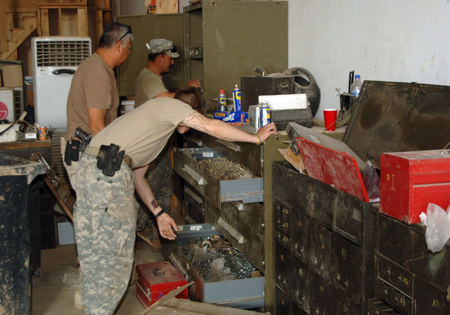 STAFF SGT. Michael Apgar, and CPL. Guage Krein, from 324th Psychological Operations Company (POC), Colo. USAR, and SGT. Felipe Capristo, from the 445th Civil Affairs Battalion, Calif. USAR, gather tools to repair a wheel on a 5 ton at the motor pool. SGT. Capristo is wearing an M9, 9 mm Beretta semiautomatic pistol. (U.S. Army photo by PFC. William Servinski II) (Released)