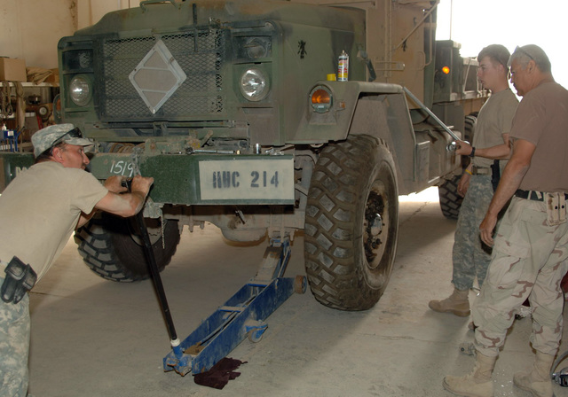 STAFF SGT. Michael Apgar, CPL. Guage Krein, from the 324th Psychological Operations Company (POC), Colo. USAR,  and SGT. Felipe Capristo, from the 445th Civil Affairs Battalion, Calif. USAR, repair the wheel from a M-923, 5-ton truck.  At the motor pool, the soldiers place the jack under the vehicle to lift the it high enough to remove the tire. (U.S. Army photo by PFC. William Servinski II) (Released)