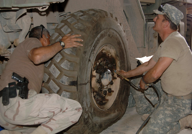 STAFF SGT. Michael Apgar, CPL. Guage Krein, from the 324th Psychological Operations Company (POC), Colo. USAR, and SGT. Felipe Capristo from the the 445th Civil Affairs Battalion, Calif. USAR, loosen the lugs from the wheel of a 5 ton vehicle. The wheel is taken off the the vehicle, at the motor pool to repair it. SGT. Felipe Capristo is wearing an M9, 9 mm Beretta semiautomatic pistol. (U.S. Army photo by PFC. William Servinski II) (Released)
