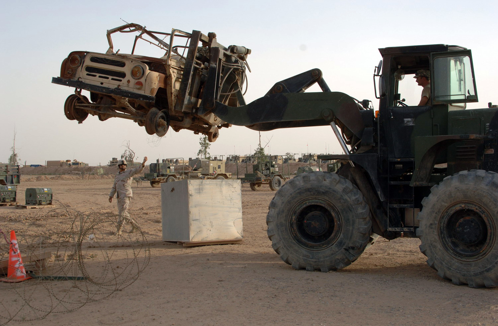 STAFF SGT. Michael Apgar, from the 324th Psychological Operations Co, (POC), Colo. USAR, operates the controls from a Rough Terrain Container Handler (RTCH) forklift vehicle, to remove a rusty, junked vehicle, from the area.  SGT. Felipe Capristo, from the 445th Civil Affairs Battalion, Calif. USAR, gives direction while ground guiding him as he lifts the vehicle. (U.S. Army photo by PFC. William Servinski II) (Released)