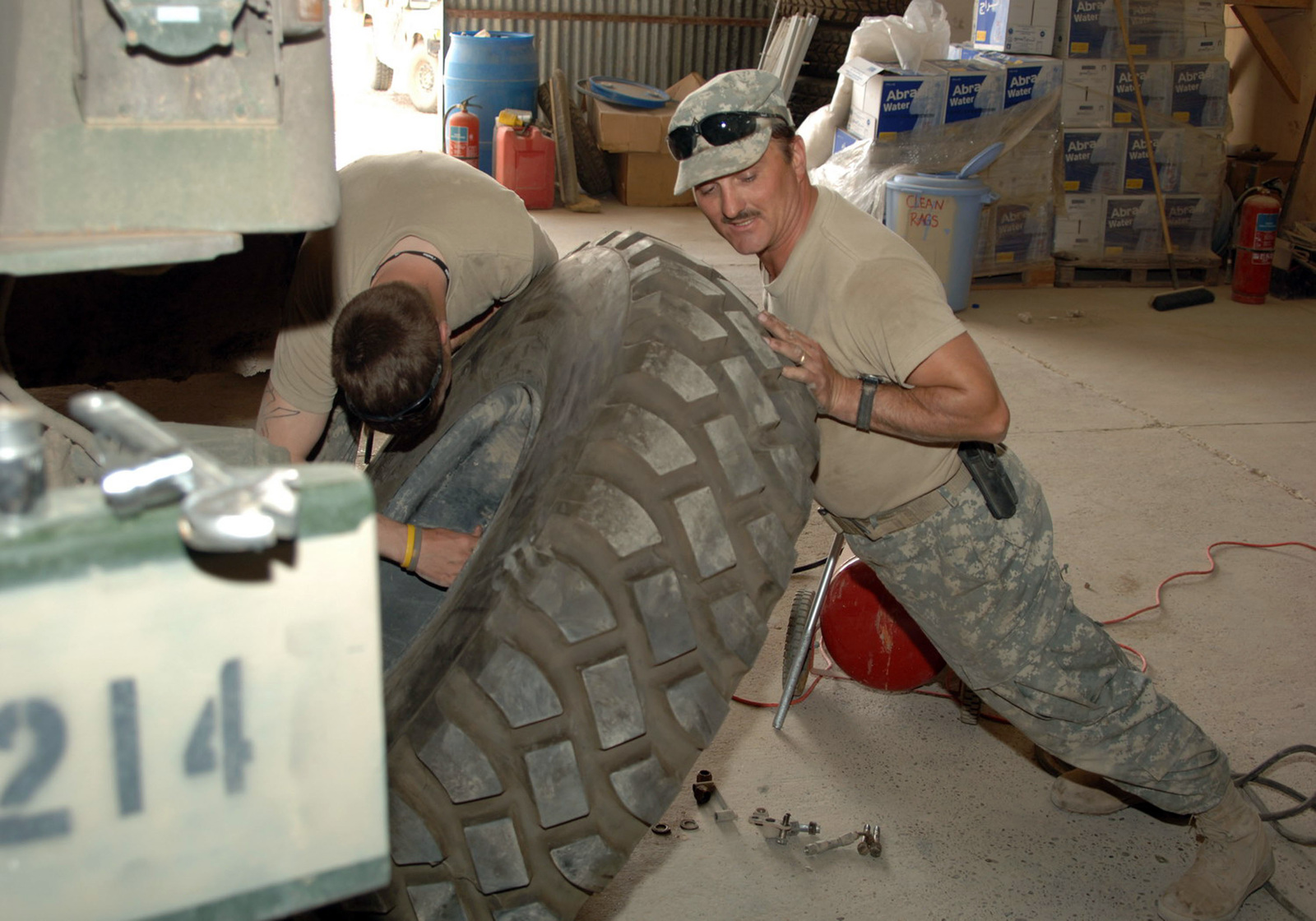 STAFF SGT. Michael Apgar (right) from the the 324th Psychological Operations Company (POC), Colo. USAR, lends his weight against the tire from a 5-ton vehicle, to hold it up, while CPL. Guage Krein, from the 324th Psychological Operations Co, (POC), Colo. USAR, works on the tire. (U.S. Army photo by PFC. William Servinski II) (Released)