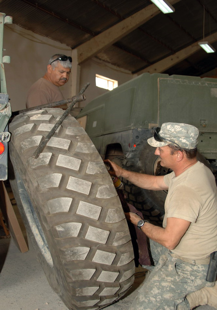STAFF SGT. Michael Apgar (right) from the the 324th Psychological Operations Company (POC), Colo. USAR, and SGT. Felipe Capristo (left) from the 445th Civil Affairs Battalion,  Calif. USAR, work together to repair a wheel from a 5 ton vehicle, at the motor pool.  The 324th is currently deployed in Iraq in support of Operation Iraqi Freedom. (U.S. Army photo by PFC. William Servinski II) (Released)