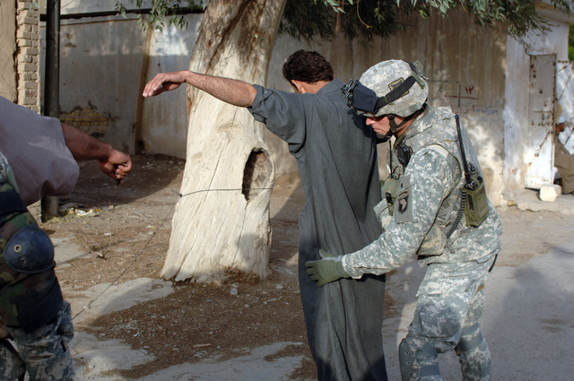 A U.S. Army Soldier of 1ST Platoon, Bravo Company, 1ST Battalion, 187th Infantry Regiment, 101st Airborne Division searches the driver while fellow Soldiers search the vehicle at a random Traffic Control Point in Bayji, Iraq on April 5, 2006.   (U.S. Army photo by SPC. Charles W. Gill) (Released)