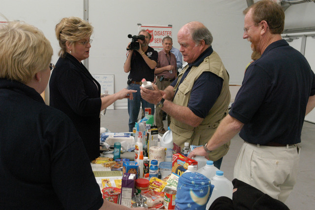 """[Hurricane Katrina] Biloxi, Miss., April 6, 2006 - Mary Lynne Miller, FEMA Acting Region IV Director, looks over items suggested to be in an evacuee's """"Go Kit"""" while FEMA Field Coordinator Marvin Davis, and FEMA Public Information Officer, Phil West, provide input, after the """"Stay Alert, Stay Alive, Hurricane Awareness 2006"""" presentation.  FEMA is a partner in state preparations for the 2006 hurricane season. George Armstrong/FEMA"""