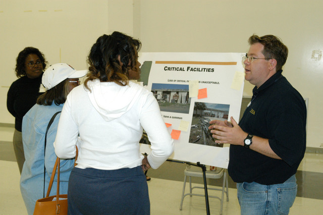 [Hurricane Katrina] Pass Christian, Miss., April 6, 2006 - Joshua Barbee, FEMA Environmental and Historic Preservation specialist, uses his experience as an architect, engineer, and planner in discussing the community need for critical facilities with a Harrison County resident.  Critical Facilities is an important component of the Harrison County Long Term Community Recovery (LTCR) plan, which will be presented to the Governor's Office of Recovery and Renewal (GORR ) by FEMA.  George Armstrong/FEMA
