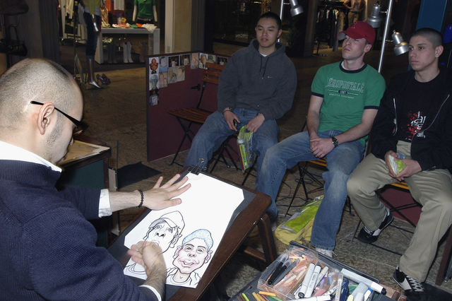 Three US Navy (USN) Sailors from the Aircraft Carrier, USS KITTY HAWK (CV 63) (not shown), have caricatures drawn of themselves by Japanese Artist Mr. Kage Nakanishi (foreground), while on a Morale, Welfare and Recreation (MWR) tour of the Venus Fort Mall, located in Tokyo, Japan. Forty KITTY HAWK Sailors participated in a free tour of Tokyo provided by the ships MWR Department as a reward for superior performance in the workplace
