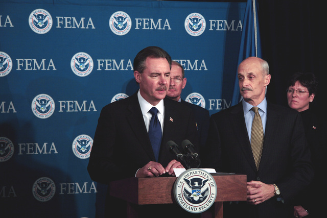Washington, DC, April 6, 2006 -- R. David Paulison accepts the FEMA Director position at FEMA Headquarters.  Behind him are Vice Admiral Harvey E. Johnson, Jr. who is now the deputy director and chief operating officer of FEMA, and Department of Homeland Security Secretary, Michael Chertoff, and Deidre Lee the new deputy director of Operations.  Bill Koplitz/FEMA