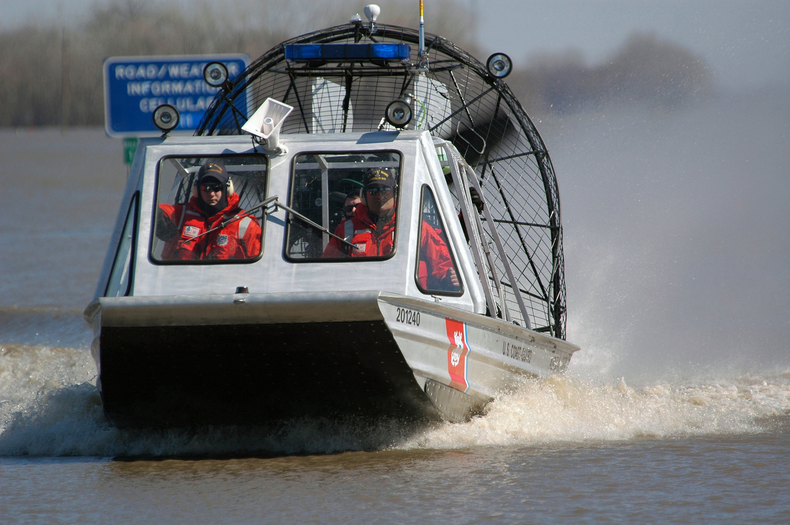 US Coast Guard (USCG) SENIOR CHIEF Boatswains Mate (BMC) Tony Hiller (right), from USCG Station Sturgeon Bay, Wisconsin (WI), pilots a USCG 20-foot Ice Boat as he navigates through flood waters covering Minnesota Highway 1, located east of Oslo, Minnesota (MN), on his way back from delivering prescription medicines and other humanitarian supplies to civilians who are stranded because the Red River has overflowed its banks and flooded the surrounding area