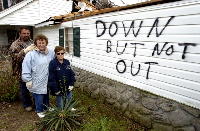 [Severe Storms and Tornadoes] Dyersburg, TN, April 09, 2006 -- A family takes a few minutes from cleaning up their tornado damaged house to stand by their optimistic motto painted on the side of their house. Leif Skoogfors/ FEMA Photo