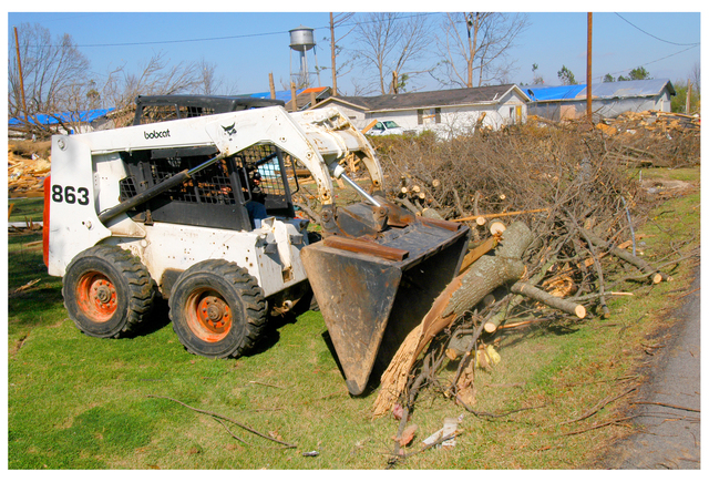 [Severe Storms and Tornadoes] Marmaduke, Ar., April 8, 2006 -- A Skid Steer moves tree debris from private property over to a street's right-of-way so county crews are able to load it onto dump trucks and haul it to a landfill. Among the losses caused by a powerful tornado that struck the community on April 2nd are hundreds of trees that once graced lawns and streets thoughout the community.  FEMA photo by Win Henderson