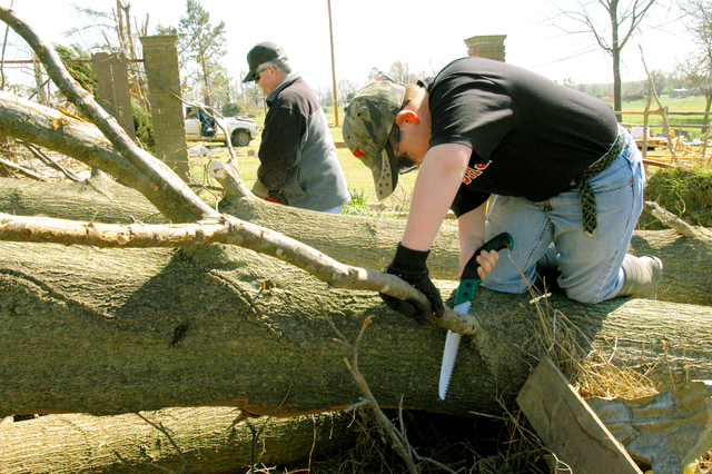 [Severe Storms and Tornadoes] Marmaduke, Ar. -- As a community pulls together to clean up the devastation left behind by an afternoon tornado on April 2nd, people - including a teenager with a pruning saw - pitch in to do their part. Seven Arkansas counties affected by severe storms and tornadoes the first three days of April are now eligible for federal disaster assistance for incurred damages and losses. FEMA photo by Win Henderson