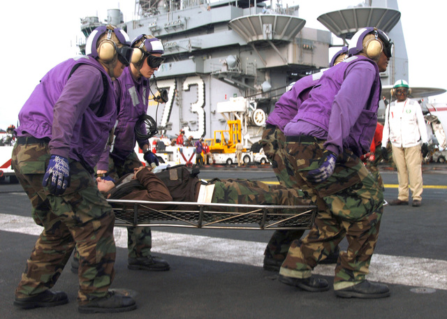 US Navy (USN) (purple shirt) Aviation Fuel Crew members stationed aboard the USN Nimitz Class Aircraft Carrier, USS GEORGE WASHINGTON (CVN 73), carry a simulated wounded shipmate across the flight deck, during Mass Casualty drill. The WASHINGTON and its Carrier Strike Group are currently underway in the Atlantic Ocean, participating in the Partnership of the Americas, a maritime training and readiness deployment with Caribbean and Latin American countries in support of the US Southern Command (SOUTHCOM) objectives for enhanced maritime security