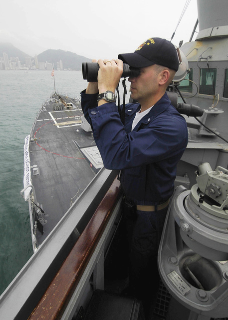 Onboard the USN Navy (USN) Arleigh Burke Class (Flight IIA): Guided Missile Destroyer (Aegis) USS SHOUP (DDG 86), USN Lieutenant Junior Grade (LTJG) Jeff Dennison, uses binoculars to monitor surface contacts in Hong Kong Harbor. The SHOUP and other ships in the LINCOLN Carrier Strike Group (LCGS) are currently in Hong Kong for a scheduled port visit