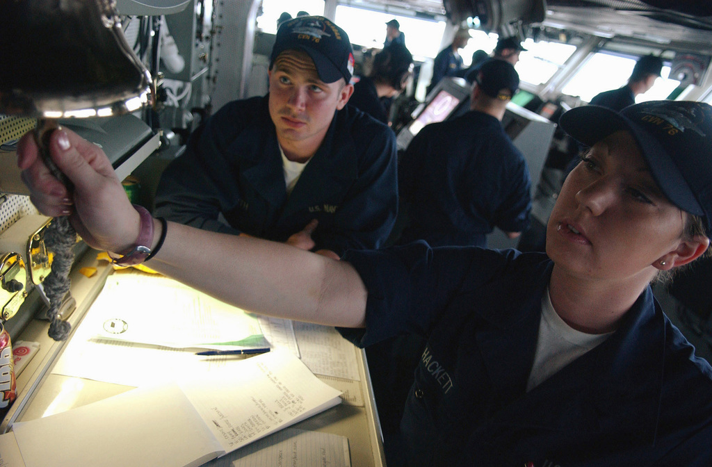 US Navy (USN) Boatswain's Mate Seamen (BMSN) Andrea M. Hackett Z (foreground), rings three bells to signal the hour of 5:30 p.m. for the crew aboard the USN Nimitz Class Aircraft Carrier, USS RONALD REAGAN (CVN 76). The REAGAN and embarked carrier Air Wing 14 (CVW-14) are currently conducting Maritime Security Operations (MSO) in the Persian Gulf region, in support of the global war on terrorism