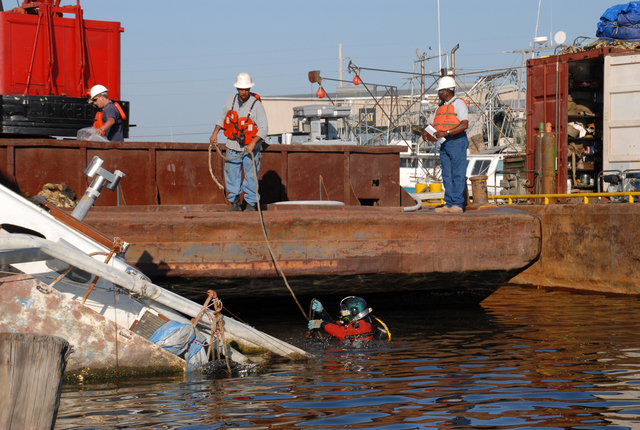 [Hurricane Katrina] New Orleans, LA, 4-10-06 -- A Diver passes a line under a Hurricane Katrina sunken boat and prepares to hand it to a Barge workman.  The U.S. Coast Guard is removing sunken boats and ships that are in the 320 miles of navigable waterways.  Marvin Nauman/FEMA photo