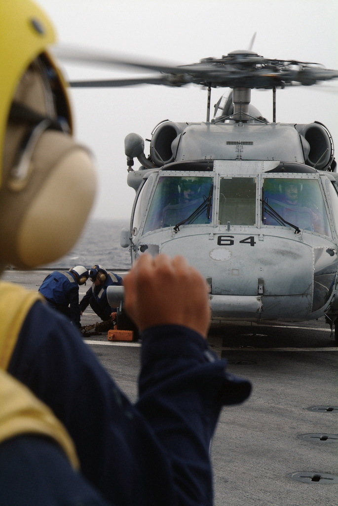 Onboard the US Navy (USN) Dock Landing Ship, USS HARPERS FERRY (LSD 49), a USN Landing Signal Enlisted (LSE) signals hold, USN SEAMAN (SN) Shannon Webb and USN Personnel SPECIALIST Third Class (PS3) Han Qin Peng, secure a SH-60 Sea Hawk Helicopter to the flight deck. The HARPERS FERRY and its crew are conducting flight deck proficiency demonstrations for an embarked Afloat Training Group as part of its Tailored Ships Training Availability, conducted while underway in the Pacific Ocean