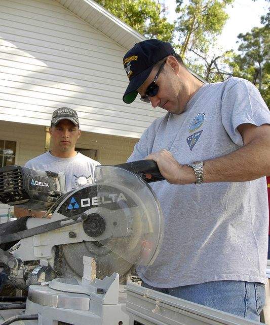 US Navy (USN) Commanding Officer (CO) of the Navy Operational Support Center (NOSC) Commander (CDR) Jeffery P. Eaton saws a baseboard while Aviation Structural Mechanic 2nd Class (AS2) Aaron Sieg observes the process during a Habitat for Humanity volunteer effort that builds houses for low-income families in Jacksonville, Florida (FL). Twenty-seven NOSC Jacksonville Sailors volunteered for this worthy cause