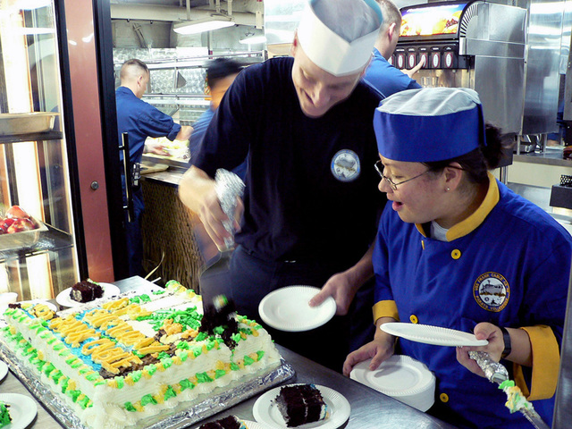 Onboard the US Navy (USN) Emory S. Land Class Submarine Tender, USS FRANK CABLE (AS 40), USN Culinary SPECIALIST Third Class (CS3) Rebecca Brucker, and Machinist's Mate Fireman (MMFN) Scott Miller, cut a cake commemorating the submarine tenders 10th Anniversary of being forward deployed to Guam