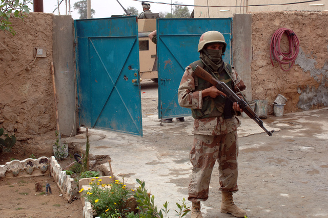 A Soldier from Charlie Company, 1ST Battalion, 1ST Brigade, 4th Iraqi Army provides security outside of a house while fellow Soldiers search for a possible weapons cache in Siniya, Iraq on April 12, 2006.   (U.S. Army photo by SPC. Charles W. Gill) (Released)