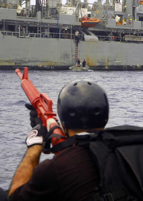 US Navy (USN) Information Systems Technician Third Class (IT3) Andre Trujillo, assigned to the Visit Board Search and Seizure (VBSS) Team from the Arleigh Burke Class (Flight II) Guided Missile Destroyer (Aegis) USS SHOUP (DDG 86), is armed with a red practice rifle, as he watches from a Rigid Hull Inflatable Boat (RHIB) as fellow members of his team board the USN Henry J. Kaiser Class Oiler, USNS WALTER S. DIEHL (T-AO 193), during a VBSS exercise. The SHOUP is currently underway in the Western Pacific Ocean operating area