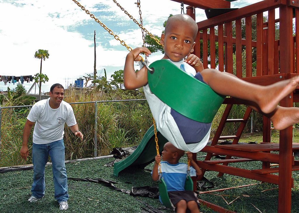 US Navy (USN) Aviation Machinist's Mate 2nd Class (AD2) Augusto Baez, assigned to Helicopter Anti-Submarine Squadron Seven (HS-7), from US Navy (USN) Nimitz Class Aircraft Carrier USS GEORGE WASHINGTON (CVN 73) plays with two local children on a swing set at the Prince William Alexander School for Special Needs Day Care playground, in Phillipsburg, Netherlands Antilles (ANT). The USN Sailors are currently participating in Partnership of the Americas, a maritime training and readiness deployment of the US Naval Forces with Caribbean and Latin American countries in support of the US Southern Command (SOUTHCOM) objectives for enhanced maritime security