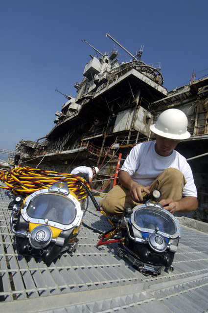 Mr. Eric Foresman, a Diver for the Resolve Marine Group, prepares and checks his equipment in preparation for an upcoming dive at Naval Air Station (NAS) Pensacola, Florida (FL).  The Divers from Resolve Marine Group are aiding in the operations as the decommissioned US Navy (USN) Intrepid Class Aircraft Carrier USS ORISKANY (CV 34), undergoes final preparations for its scheduled sinking. The ORISKANY will become the largest ship ever intentionally sunk as an artificial reef. After ORISKANY reaches the bottom, ownership of the vessel will transfer from the USN to the State of Florida