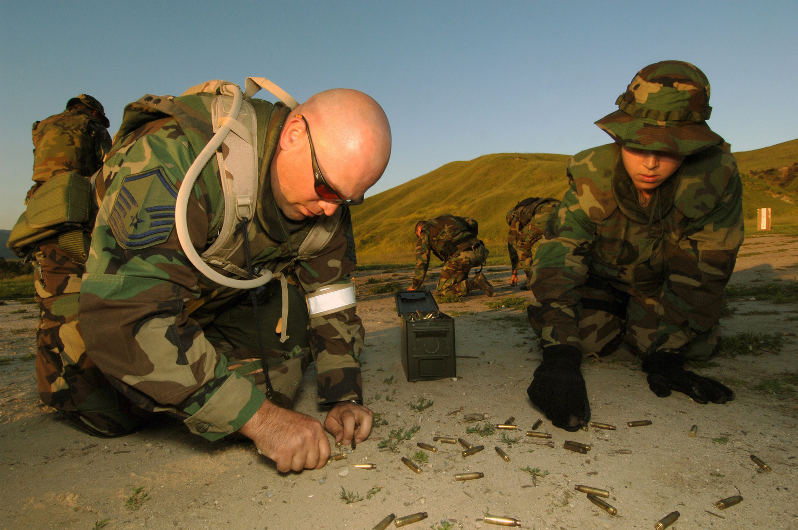 US Air Force (USAF) MASTER Sergeant (MSGT) Richard Inman (left) and US Navy (USN) Journalist Second Class (JO2) Brooke Armato pick up brass shell casings after a successful joint force weapons exercise conducted at Marine Corps Base (MCB) Camp Pendleton, California (CA). The bi-annual Quick Shot field exercise enhances the combat photographers' war fighting capabilities, including combat documentation, and a variety of tactical skills. Conducting Joint Operations with Air Force Combat Camera is the primary focus of this exercise