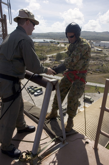 "US Navy (USN) CHIEF PETTY Officer (CPO) Jeremy Logan (left), assigned to Explosive Ordnance Disposal Mobile Unit 5 (EODMU-5) gives last-minute advice to Royal Australian Navy (RAN) Lieutenant Commander (LCDR) Michael Maley, before he goes over the side of a wall during a fast rope exercise conducted at Santa Rita Naval Base, Guam (GU), during the Annual Multi-national Explosive Ordnance Disposal (EOD) Exercise known as TRICARB 2006."" The Exercise brings together EOD Units from the US, Australia and Singapore"