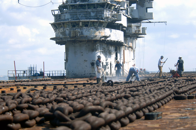 Civilian employee with the Resolve Marine Group, lay out the anchor chain on the flight deck aboard the decommissioned US Navy (USN) Intrepid Class Aircraft Carrier USS ORISKANY (CV 34), as the Carrier undergoes final preparations for its scheduled sinking, while moored to the pier at Naval Air Station (NAS) Pensacola, Florida (FL). The ORISKANY will be towed 22-miles south of Pensacola in approximately 212-ft. of water where it will become the largest ship ever intentionally sunk as an artificial reef. After ORISKANY reaches the bottom, ownership of the vessel will transfer from the USN to the State of Florida