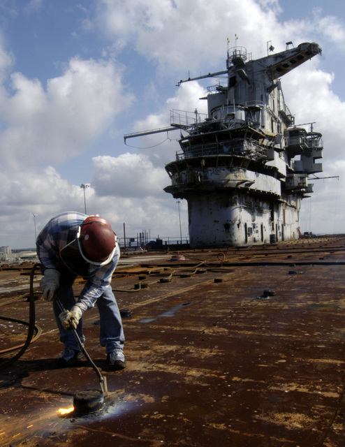 Onboard the flight deck decommissioned US Navy (USN) Intrepid Class Aircraft Carrier USS ORISKANY (CV 34), Mr. Joe Olvera, an employee with the Resolve Marine Group, clears away the portions of the deck during maintenance as the Carrier undergoes final preparations for its scheduled sinking, while moored to the pier at Naval Air Station (NAS) Pensacola, Florida (FL). The ORISKANY will be towed 22-miles south of Pensacola in approximately 212-ft. of water where it will become the largest ship ever intentionally sunk as an artificial reef.  After ORISKANY reaches the bottom, ownership of the vessel will transfer from the USN to the State of Florida