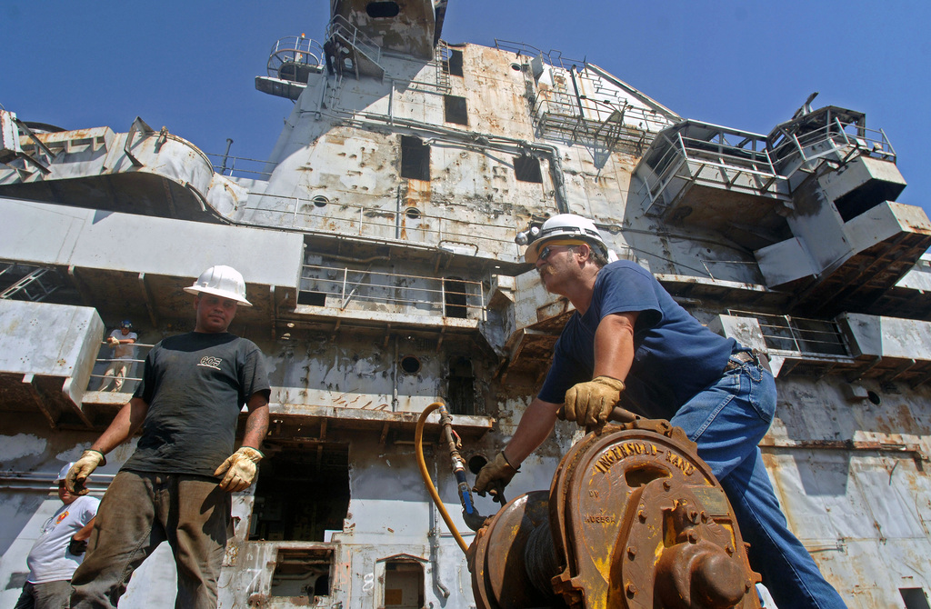 Resolve Marine Group employees, Mr. Aaron Nahapetian (left), and Mr. Robert Lee Jr. begin pulling cable in off the flilght deck of USS ORISKANY (CVA-34) during preparations to sink the vessel, conducted at Naval Air Station (NAS) Pensacola, Florida (FL). The ORISKANY is schedule to be scuttled 22 miles south of Florida in approximately 212 feet of water in the Gulf of Mexico where it will become the largest ship ever intentionally sunk as an artificial reef. After the ORISKANY reaches the bottom, ownership of the vessel will transfer from the Navy to the State of Florida
