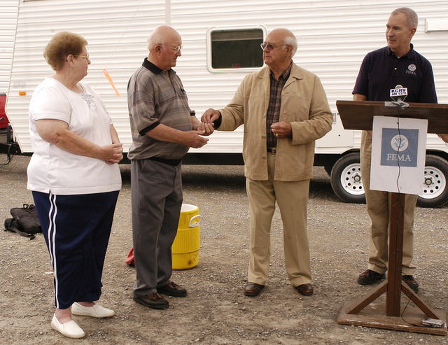 [Severe Storms, Tornadoes, and Flooding] Caruthersville, MO, 4-20-06 -- FCO Tom Costello watches as Presiding Commissioner Charlie Mass presents the keys to a new manufactured home to Donna and Joe Crain to use as temporary housing.  The Crain family lost their home when a tornado hit the town on April 2, 2006.  Photo by Patsy Lynch/FEMA