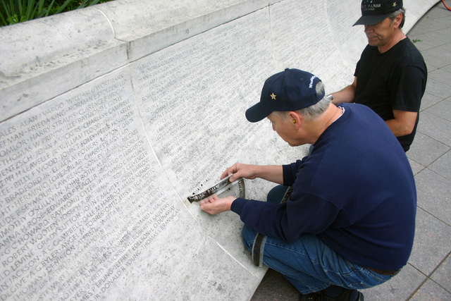 James Lee, Great Panes Glassworks, removes the stencil after adding the name of Naval Criminal Investigative Service (NCIS) Special Agent (SA) Thomas P. Marzilli to the National Law Enforcement Officer's Memorial in Washington District of Columbia (DC). NCIS SA Marzilli will be among many officers honored during Police Week events in the nations capitol