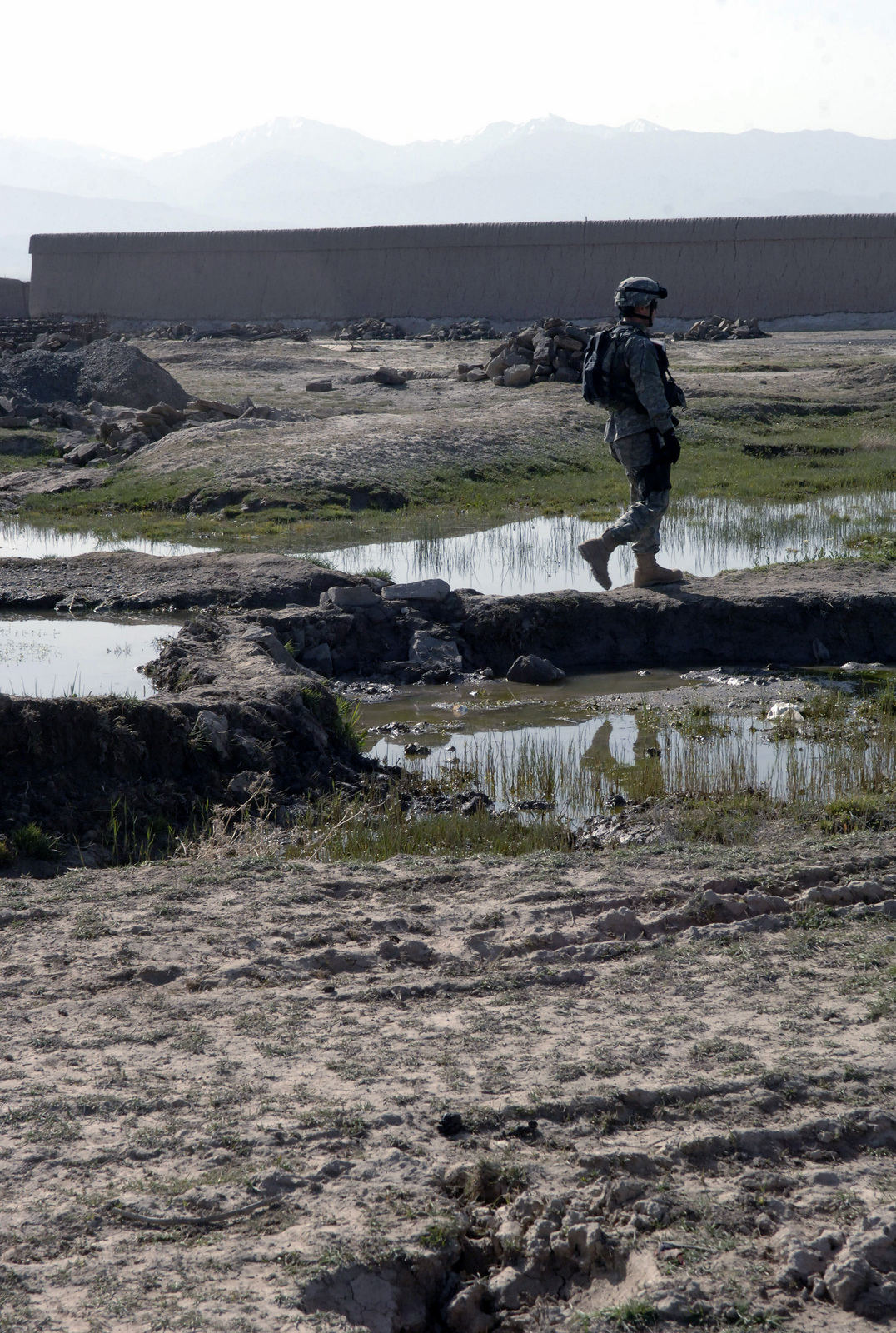 US Navy Machinist's Mate First Class (MM1) Caleb Duke, assigned to the US Army (USA) 10th Mountain Division, conducts a dismounted patrol through the countryside during a search of the local area in Zormat, Afghanistan, during Operation ENDURING FREEDOM