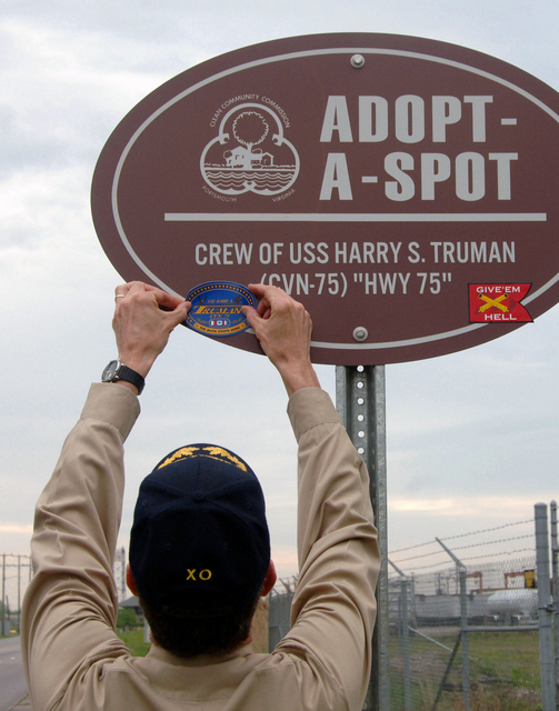 US Navy (USN) Captain (CAPT) Paul Monger Executive Officer, of the USN Nimitz Class Aircraft Carrier USS HARRY S. TRUMAN (CVN 75) places a TRUMAN sticker on the ship's new Adopt-A-Spot sign. More than 150 Sailors from TRUMAN picked up trash on Elm Avenue in Portsmouth, Virginia (VA) as part of the TRUMAN's participation in the city's Adopt-A-Spot program and in celebration of Earth Day