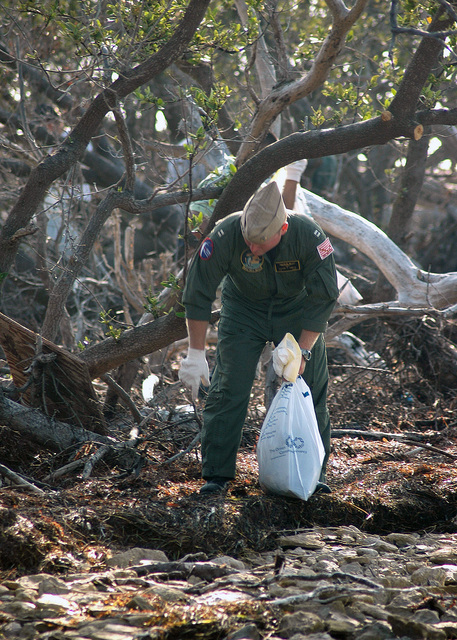 US Navy (USN) Lieutenant (LT) Dave Smith, a Search And Rescue (SAR) Pilot, stationed at Naval Air Station (NAS) Key West, Florida (FL), picks up trash on the beach outside NAS Key West as he participates in the base annual Earth Day beach cleanup program