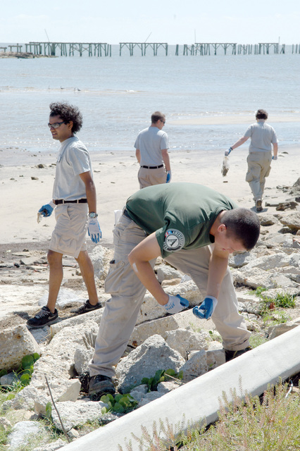 [Hurricane Katrina] Waveland, Miss., April 22, 2006 -- AmeriCorps*NCCC Team Leader David Celata picks up debris along Waveland's beachfront.  Five hundred NCCC members cleared beaches and culverts and performed other volunteer work, on National and Global Youth Services Day today.  George Armstrong/FEMA