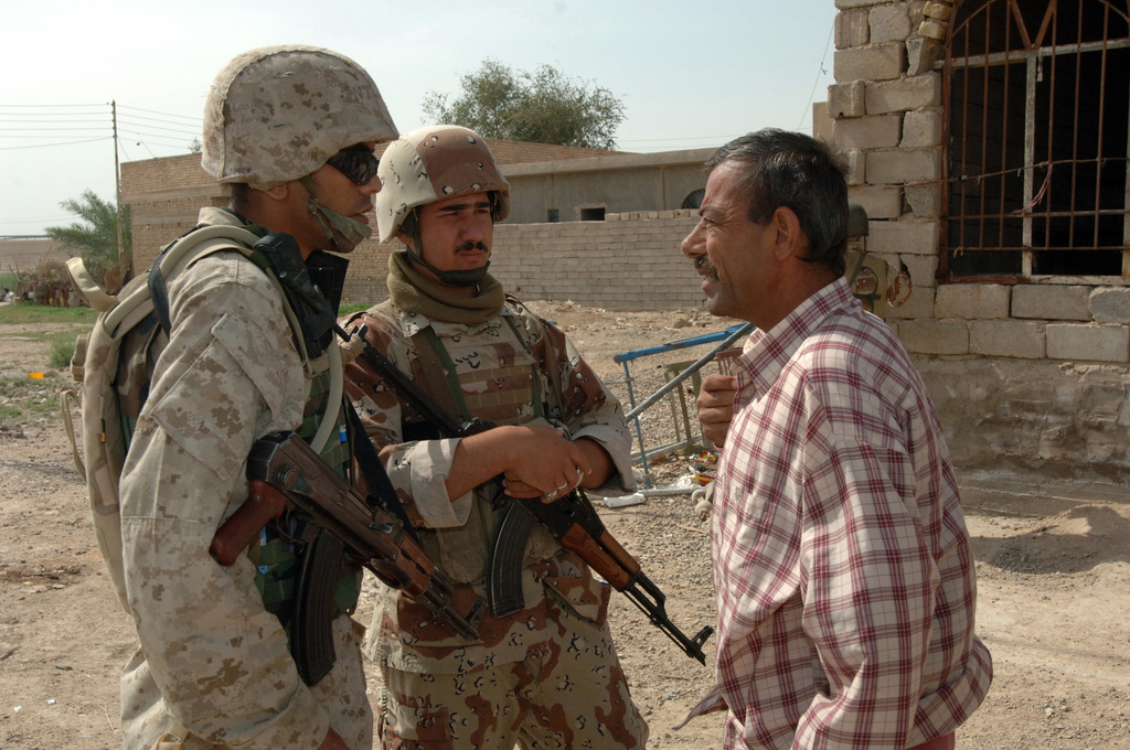 Iraqi Soldiers from the 4th Iraqi Army Brigade and U.S. Marines from Charlie, 1ST Battalion, 1ST Marine Regiment conduct a joint patrol in Khandari, Iraq on April 22, 2006. The purpose of the patrol was to capture suspects from a joint watch list and to give the local people a feeling of security. A man is questioned by an Iraqi Army soldier about the climate of his neighborhood.(U.S. Army photo by STAFF SGT. Kevin L. Moses Sr.) (Released)