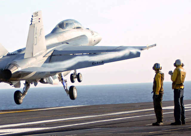Two US Navy (USN) (yellow shirt) Plane Directors observe as a USN F/A-18F Super Hornet aircraft executes a touch and go exercise on the flight deck aboard the Nimitz Class Aircraft Carrier, USS THEODORE ROOSEVELT (CVN 71), while the ship is underway in the Atlantic Ocean, conducting qualifications as part of the fleet response plan