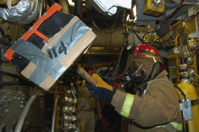 Onboard the US Navy (USN) Aircraft Carrier, USS KITTY HAWK (CV 63), a Sailor simulates removing lagging material from a steam pipe during an engineering main space fire drill. Sailors train to defend the ship and control battle damage during such drills. The KITTY HAWK is currently in port at Yokosuka, Japan