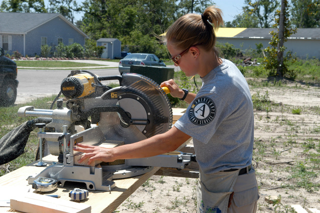 [Hurricane Katrina] Gulfport, Miss., April 27, 2006 - AmeriCorps*NCCC member Meredith MacMillan of Hudson, Ohio operates a saw at a Harrison County Habitat for Humanity work site.  AmeriCorps*NCCC is partnering with Harrison County Habitat to build bunkhouses for Gulf Coast recovery volunteers.  George Armstrong/FEMA