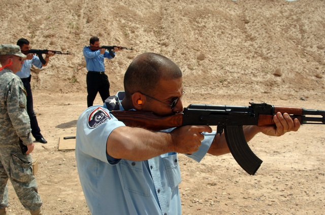 Iraqi Police men shoot AK-47 while U.S. Army STAFF SGT. Michael Ledbetter observes, during a firing training at Forward Operating Base Remagen, Tikrit on April 27, 2006.   Ledbetter is assigned to 3-187th Infantry Regiment and is in charge of training the local Iraqi police in Forward Operating Base Remagen.  The 101st Airborne Division is currently deployed in the Tikrit area and Northern Iraq on support of Operation Iraqi Freedom. (U.S. Army photo by SPC. Teddy Wade) (Released)